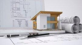 plastico di una casa indipendente, progetti cartacei arrotolati, penne da architetto