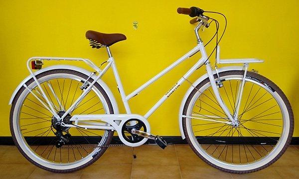 Bicicletta bianca di doppia barra con porta paniere anteriore e dietro e luci