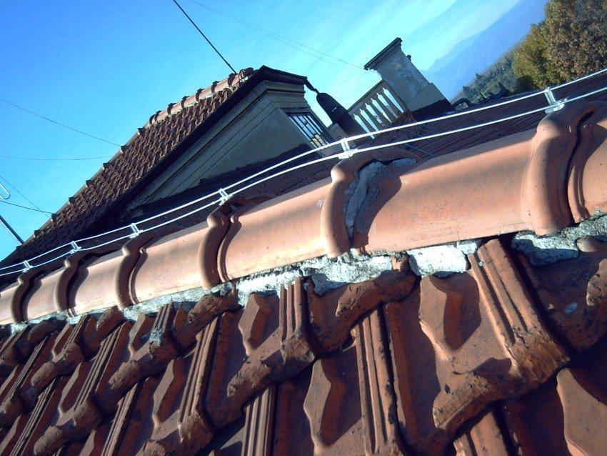 close up di dissuasore elettrico per piccioni e gabbiani installato sul tetto di una abitazione civile
