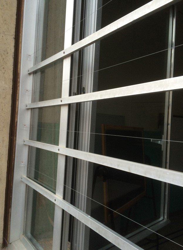 fili ballerini per piccioni su grate di finestra