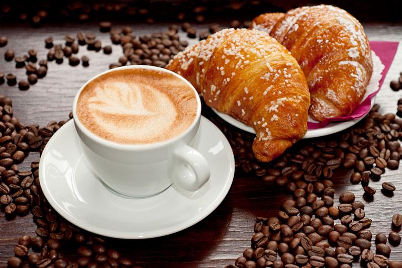 Una tazza di cappuccino con accanto due brioches su un piatto e sulla tavola dei chicchi di caffe'