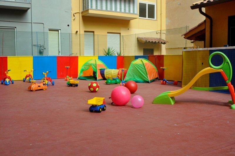 spazio gioco esterno con casa gialla di sfondo
