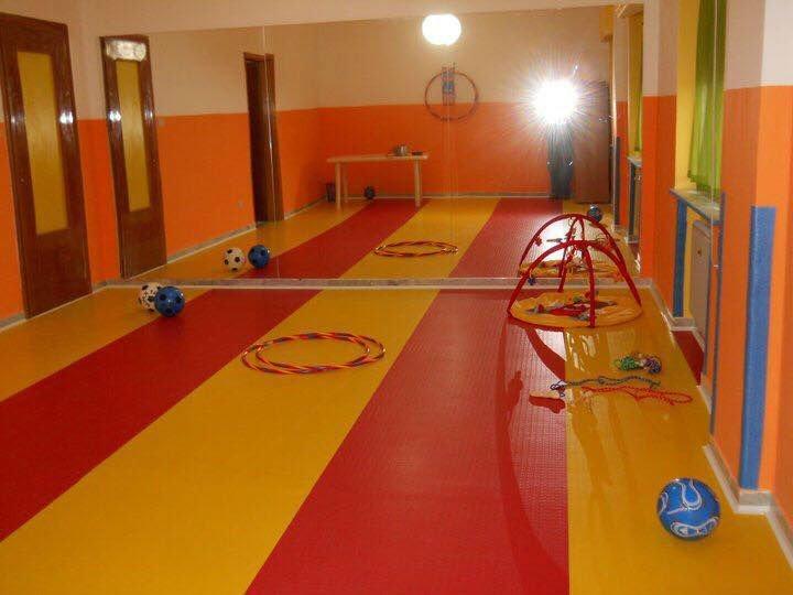 degli hula hoop, palloni e altri giochi per bambini in un ampia stanza