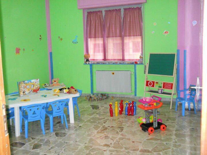 un tavolino con delle sedie azzurre, birilli e altri giochi per bambini
