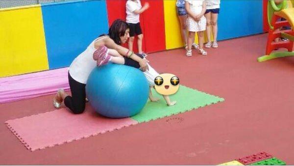 una ragazza che fa giocare una bambina su una paqlla medica