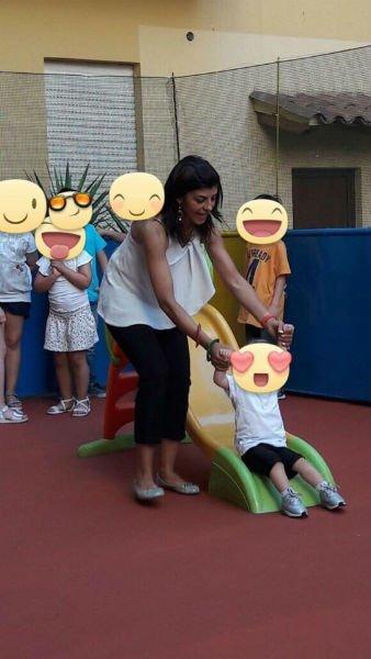 una donna che tiene una bambina mentre scende dallo scivolo