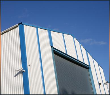 Un grande capannone industriale con entrata chiusa da una serranda avvolgibile in metallo