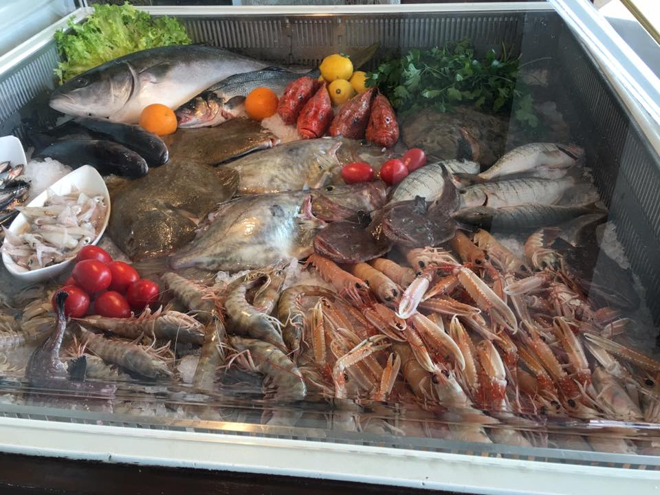 diversi tipi di pesce con verdure e pomodori