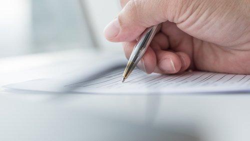 mano con penna mentre scrive