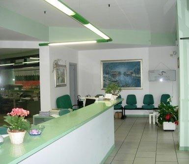 sala d'attesa con poltrone verdi e banco d'accettazione