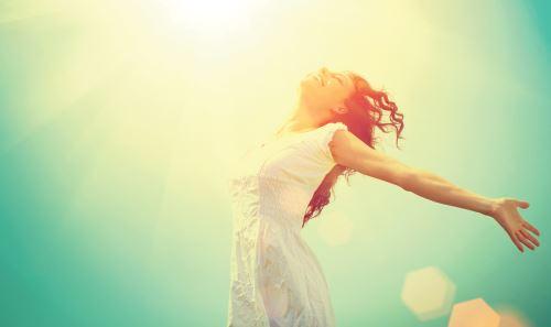 una donna a  braccia aperte sotto il sole