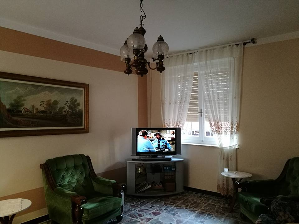 vista angolare di una stanza con televisione, poltroni e tenda trasparente su finestra