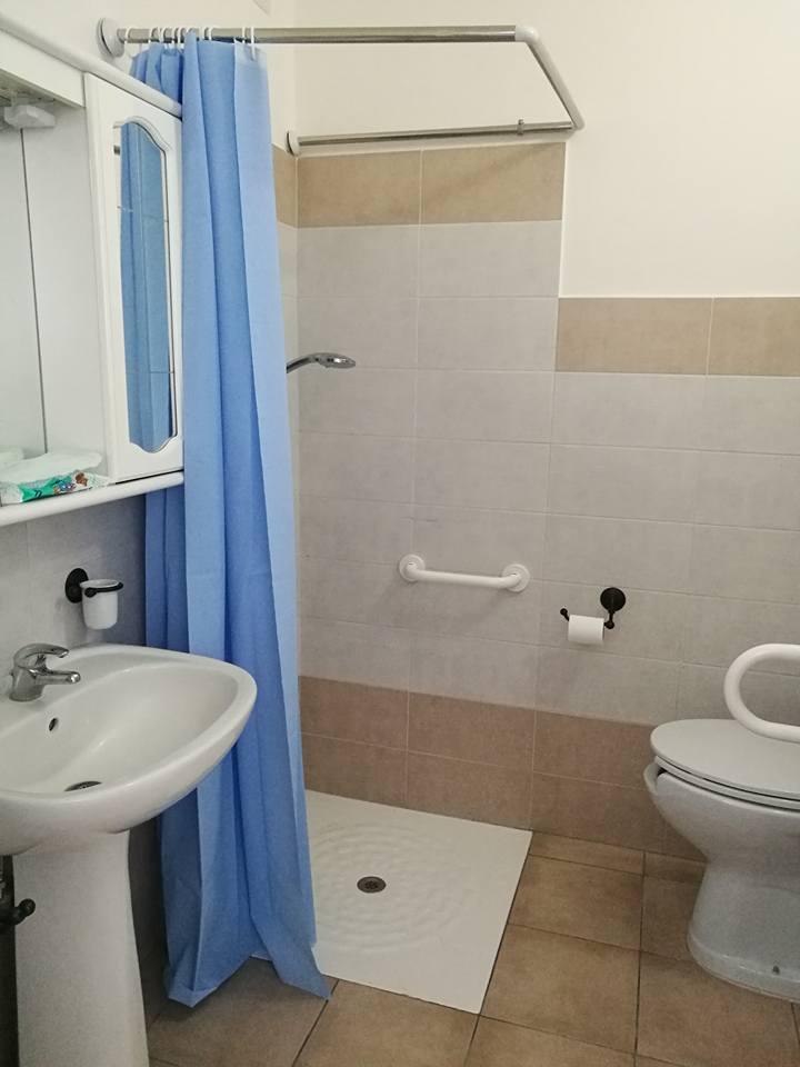 vista interna di un bagno con lavabo, specchio e bide