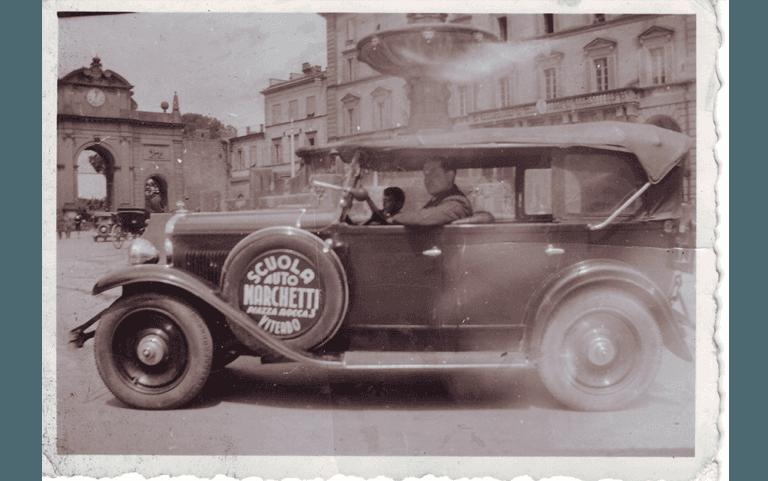 Foto bianco e nero auto storica con logo Autoscuola Marchetti