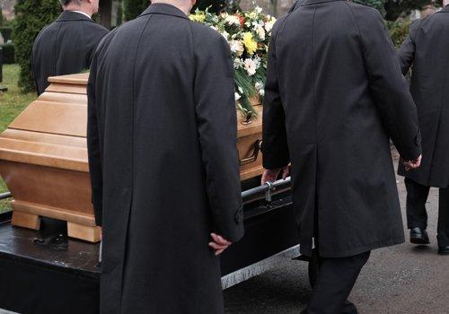 uomini in nero che accompagnano il feretro