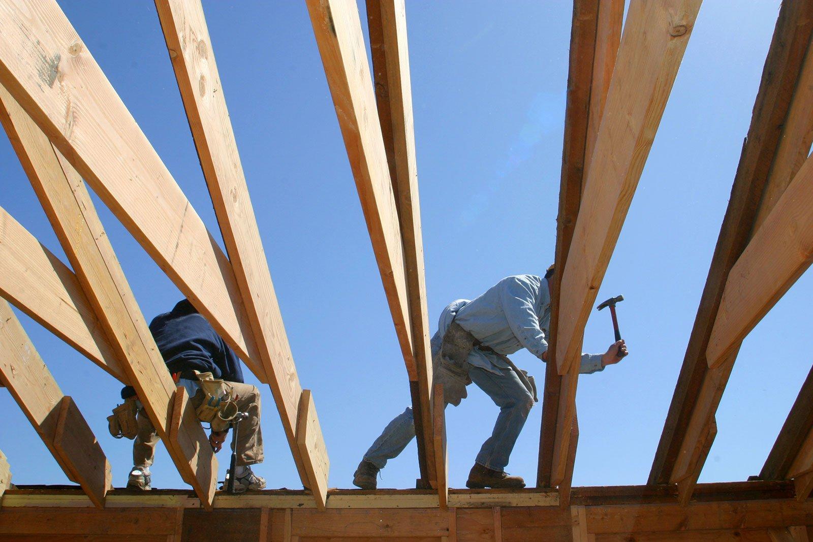 degli uomini in piedi su un tetto con dei martelli e vista delle travi di legno