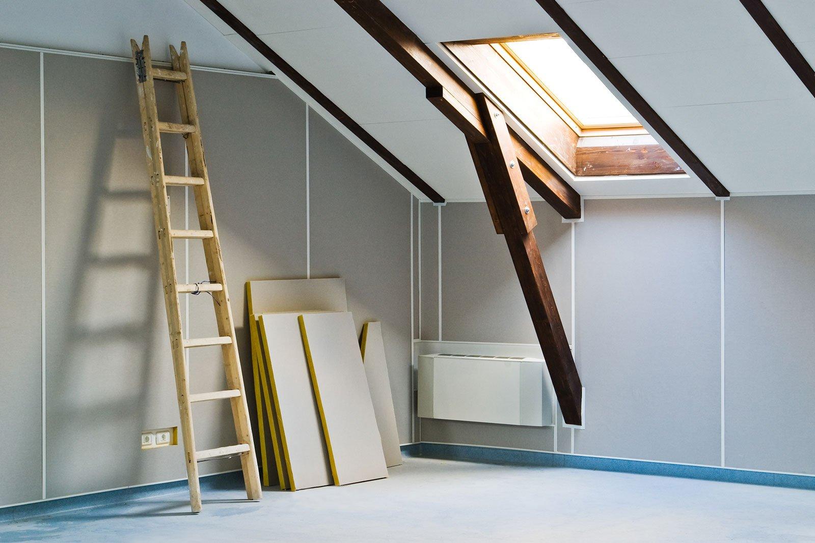 una mansarda con una sala appoggiata al muro, delle assi e un lucernario