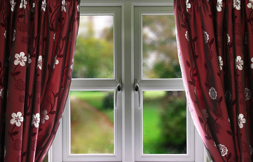A small uPVC window with red curtains