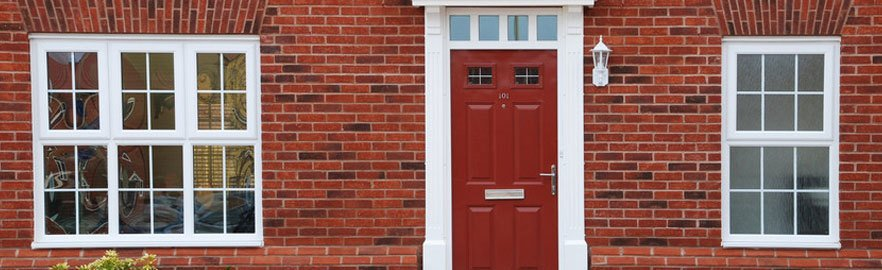 A red front door with newly installed windows on either side