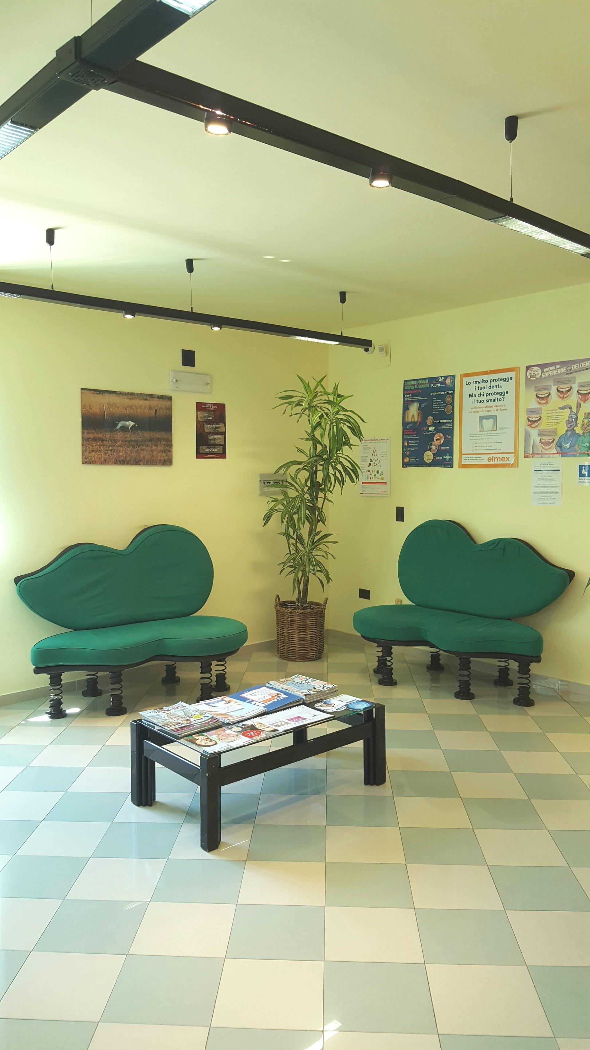 sala d'attesa con due poltrone verdi e un tavolino