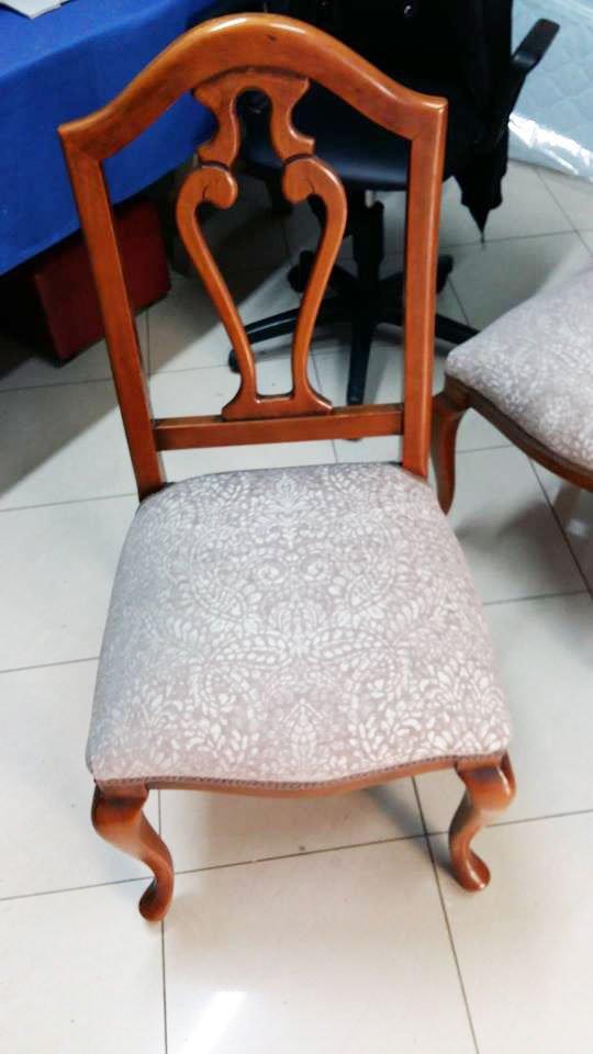 una sedia marrone rivestita con una stoffa bianca a disegni grigi