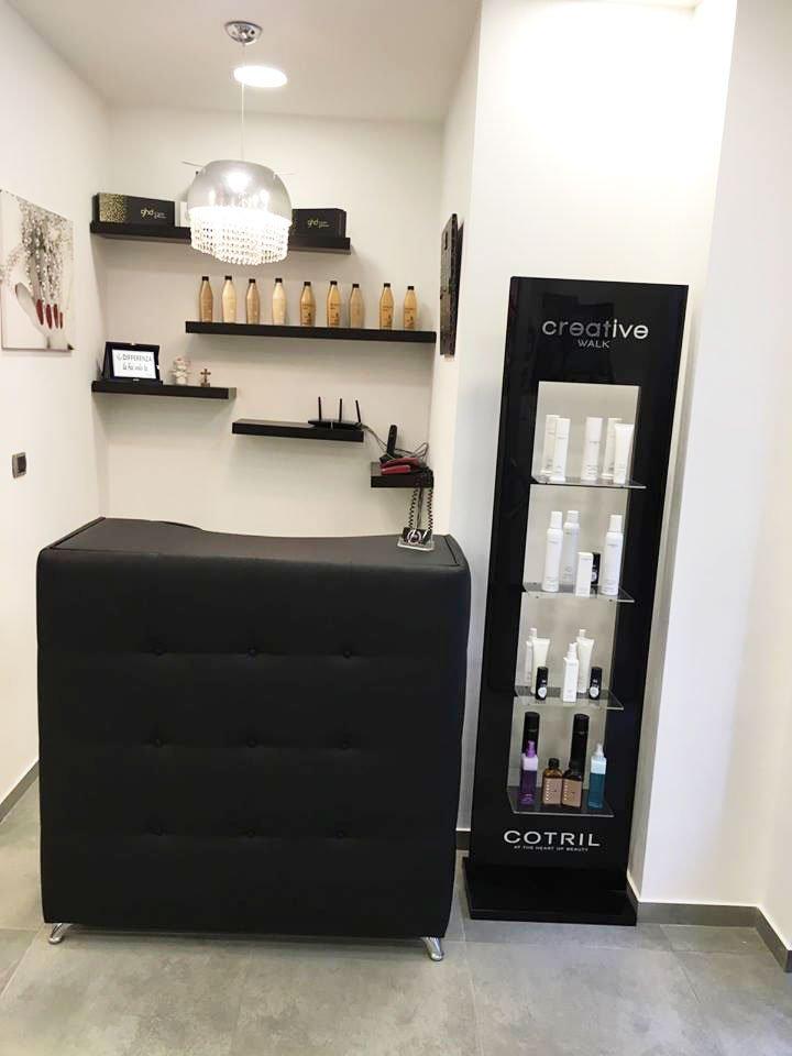 vista di un bancone da reception nero in pelle  e accanto una vetrina nera con dentro dei prodotti