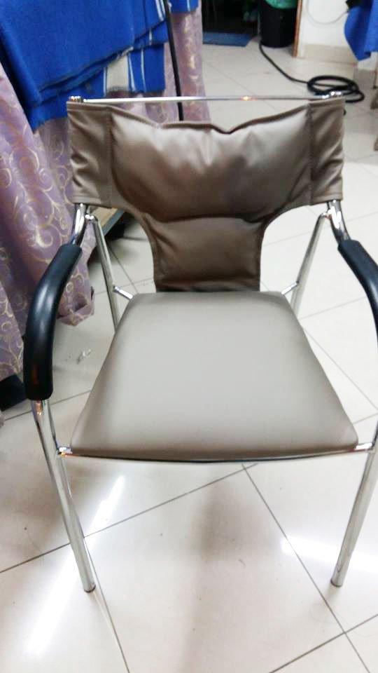 una sedia in acciaio con schienale e cuscino di color beige e manici in plastica nera