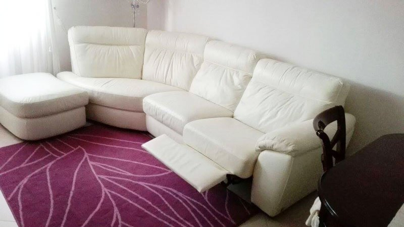 un divano in pelle angolare di color bianco reclinabile e davanti un tappeto viola con disegni bianchi