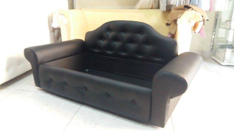 Un divano di pelle di color nero e dietro la scatola di imballaggio
