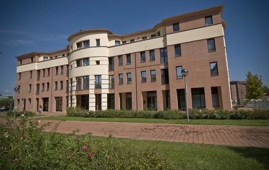 Vista dell'edificio sede dello studio e del cammino di accesso allo stesso circondato di erba ,siepi e piante