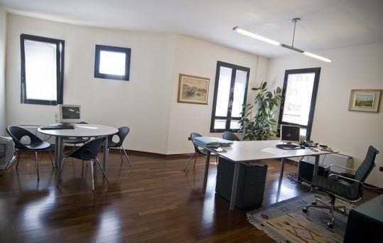 Ufficio con due tavoli di lavoro di colore bianco e le sedie di colore grigio al pari delle finestre