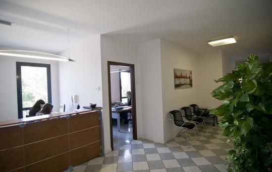Bancone della reception e sala d'attesa con sedie nere