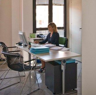 Partner scrivendo nel computer ha dossier nella tavola di colore bianco
