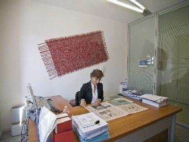 Partner leggendo il gazzetta nella tavola di loro ufficio che ha diversi libri e dossier