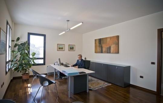 Ufficio con una grande tavola bianca, mobili e finestre grigie e tabella in toni bruni pende dalla parete