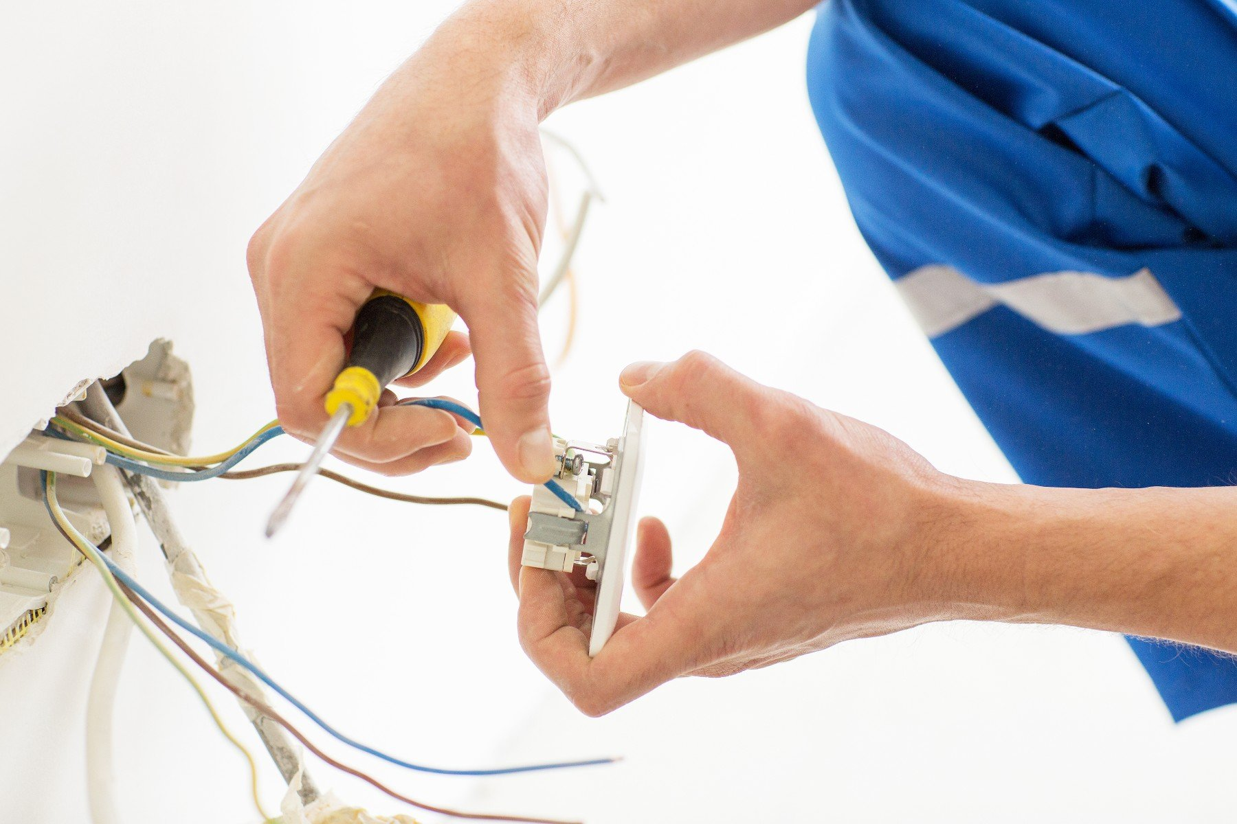 close up of electrician hands with screwdriver fixing socke