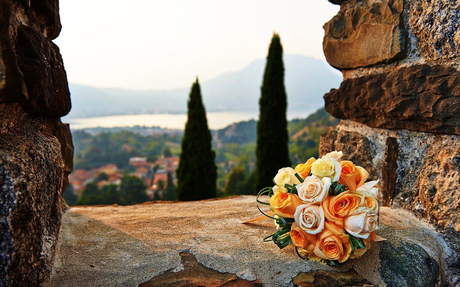Mazzo di rose bianche,gialle e arance su un muro di pietra