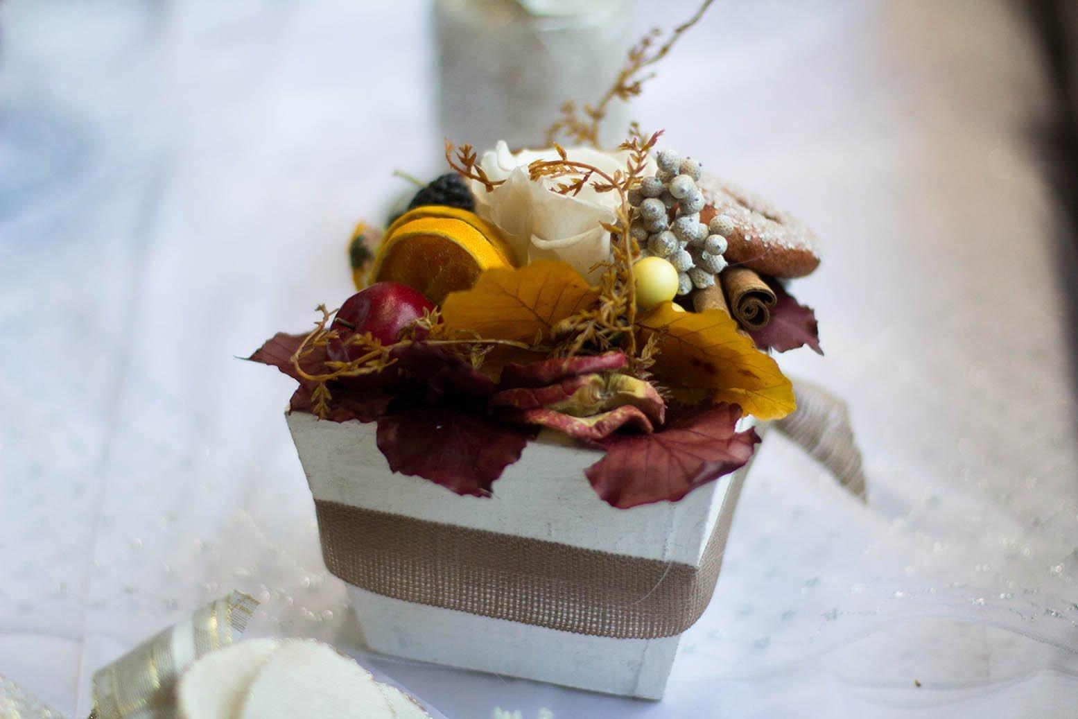 Centro con una rosa blanca, mela, arancione, vaniglia e frutti del bosco