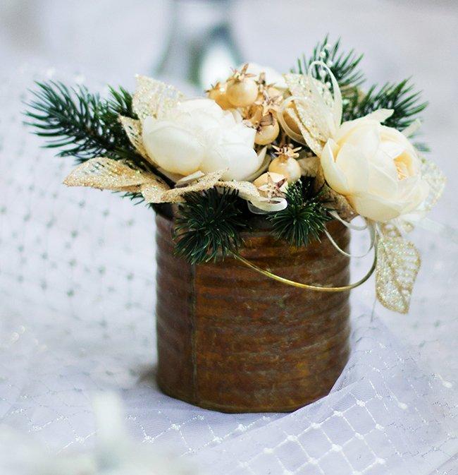 Centro di fiori bianchi e dorato con foglie di pino