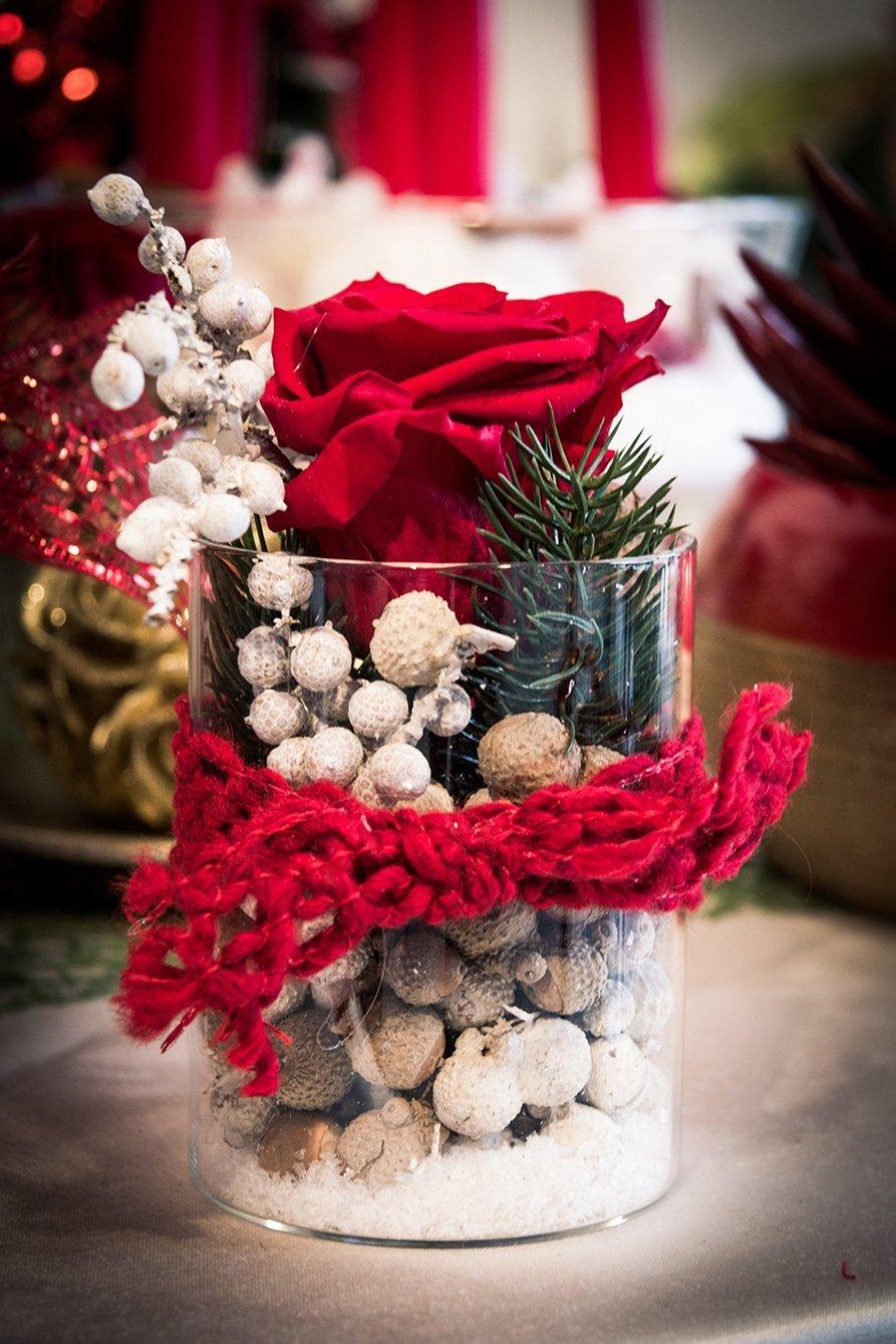 Vaso con nocciole, foglie di pino, una rosa rossa e un laccio rosso