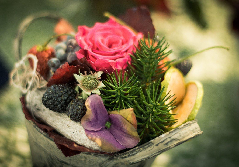 Ornamento de natale con una rosa rossa,frutti del bosco,foglie secche e foglie di pino