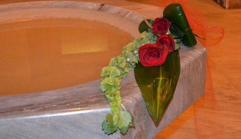 Composizione verde con tre rosa rossa
