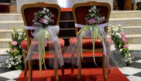 Ramos di rose bianche e una rosa legati nella parte posteriore delle sedie dei fidanzati