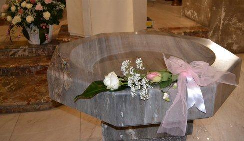 Ramo rosa e bianco con laccio rosa collocato nella fonte battesimale