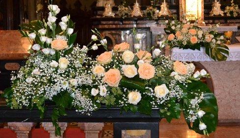 Rose bianche e rosa pallido depositate presso l'altare