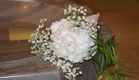 Mazzo di fiori bianchi nella fonte battesimale