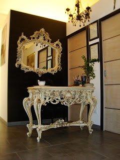 uno specchio al muro e un tavolino di color bianco e dorato