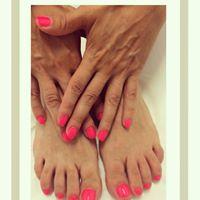 delle mani e dei piedi con lo smalto di color fucsia