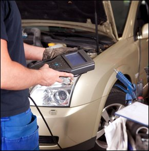 Auto electrician looking at car diagnostic device
