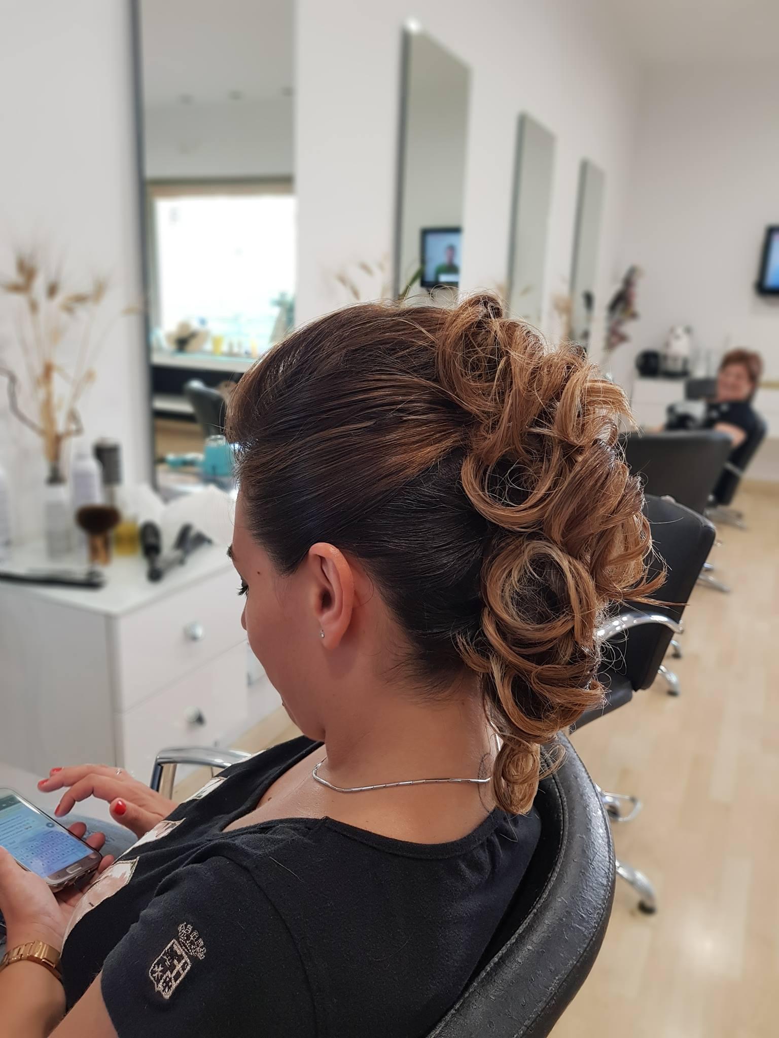 Parrucchiere spruzza lacca sui capelli della cliente.